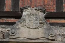 Wappen befindet sich an einem Gebäude auf dem Gutshof